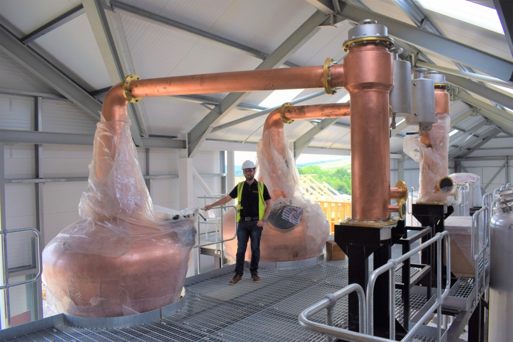 Josh Office Manager beside new stills at GlenWyvis Distillery